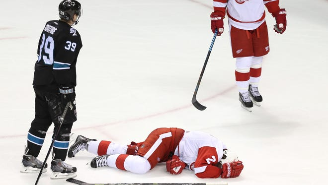 Detroit Red Wings defenseman Brendan Smith lies on the ice in front of San Jose Sharks center Logan Couture, left, after being injured during the third period.
