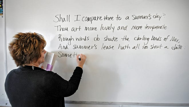 """Cathedral High School English teacher Michelle Voit copies a popular sonnet by Shakespeare onto the white board in her classroom Wednesday. She suggests those new to the genre start with the last word of a line and work backward. """"Vows"""" rhymes with """"cows,"""" she said when prompted for lines that might relate to Stearns County."""