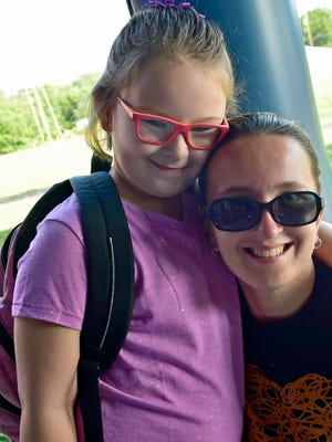 Hope Langenstein, 7, gets a hug from her mom, Christiana Late, before entering the building Thursday, August 18, 2016 at the new Marion Elementary School.