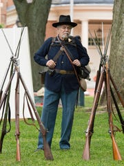 Ty Magliola of Frankford with 2nd Delaware stands next to their rifles during the Old Dover Days parade in downtown Dover.