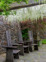 Fashioned from black locust planks, Dan Benarcik's high-backed chairs at the Pond Arbor are minimalist in conception, and their spare lines are clean and rustic against the mosaiclike stonework.