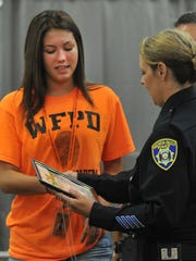 Wichita Falls Junior Citizens Police Academy student Chryssy Dumas receives her graduation certificate Friday morning during the Wichita Falls Police Departments Junior Police Academy's graduation ceremony held at the downtown library.