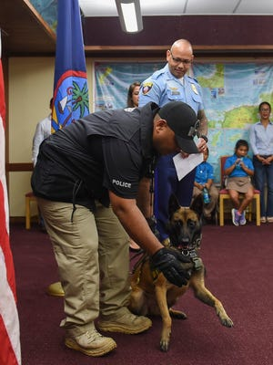 Guam Police Department Officer Andrew R. Atoigue gives a demonstration with explosives detection canine, Kuro, a Belgian Malinois, during a recognition ceremony for the Guam Homeland Security Office of Civil Defense and GPD at the Ricardo J. Bordallo Governor's Complex in Adelup on Nov. 3, 2017.