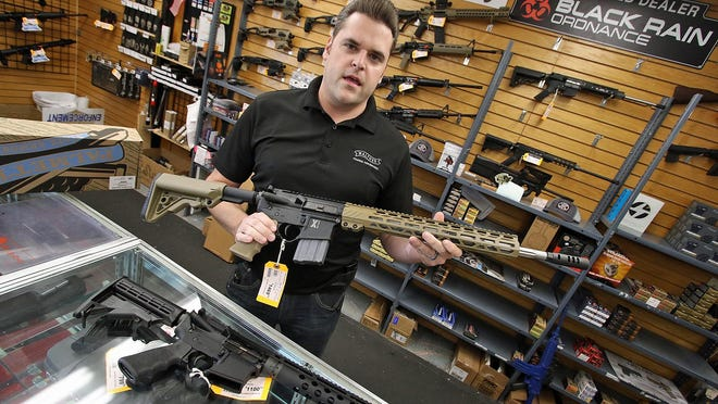 Quniton Thompson shows off a Rock River Arms 5.56 MM AR-15 Friday afternoon, Nov. 6, 2020, at Shooters Express on Caldwell Drive in Belmont.