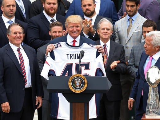 cdaa6f54c President Donald Trump (M) holds a team jersey as New