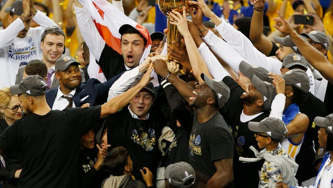 Golden State Warriors players and staff hold up the Larry O'Brien Trophy after defeating the Cleveland Cavaliers in game five of the 2017 NBA Finals at Oracle Arena.