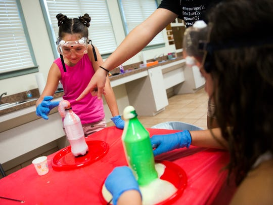 Madison Tracey, 11, watches the chemical reaction between yeast, hydrogen peroxide and dish soap during a hands on workshop for young girls on Saturday, September 2, 2017 at the Naples Girl Scout House in Cambier Park. Emily Hugan, 17, is working for her Gold Award in troop 477 with her project, Sisters in Strength.