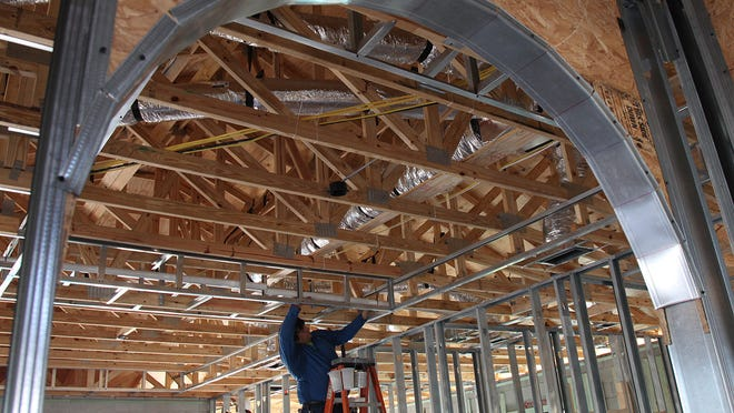 A sub-contractor with Vitex installs wiring in a home under construction in Gateway recently. News-Press Market Watch forecasters say home construction in 2015 could be weaker than it was last year.