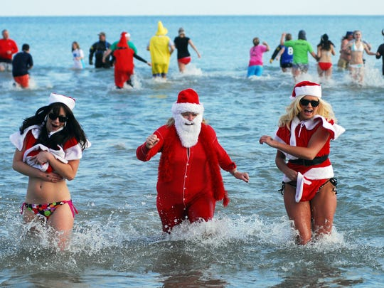 A very chilly Santa Claus and a pair of cool elves sprint from the water at Lakeside Park during the Kiwanis Polar Bear Plunge. The annual fundraiser features a costume contest, warming fire, coffee and hot cocoa.