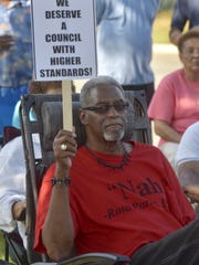 Milton resident Donald Brown holds a sign during a