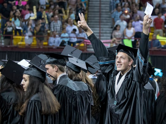 Alex Lemke reacts as he finds his family during the opening procession at the Oñate High School graduation held May 19, 2018, at the Pan American Center.