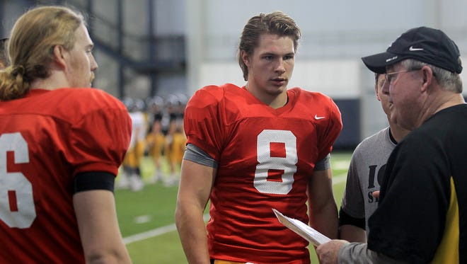 Iowa quarterbacks C.J. Beathard, left, and Tyler Wiegers talk with offensive coordinator and quarterbacks coach Greg Davis during practice at the indoor practice facility on Wednesday, April 1, 2015.