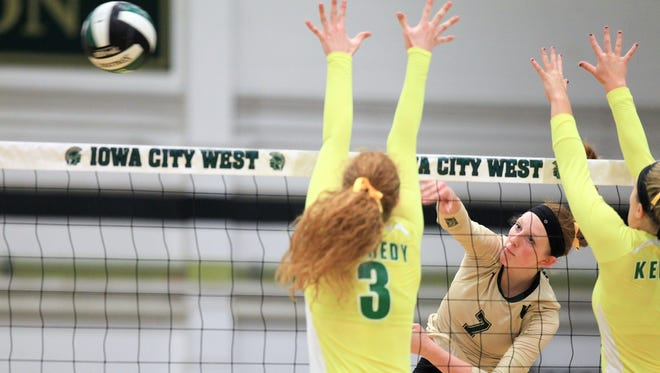 West High's Emma Norris goes for a kill during the Women of Troy's game against Cedar Rapids Kennedy on Tuesday, Sept. 22, 2015.