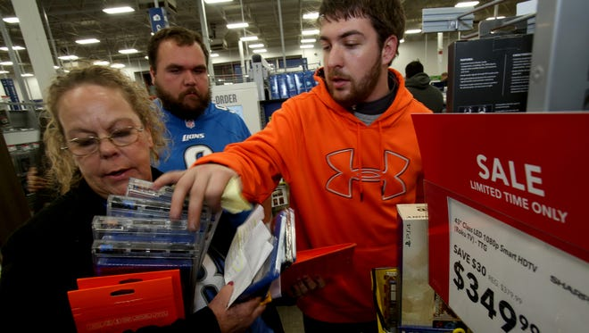 Ruth VonRusten, 51 of Warren, left to right, holds movies and video games as her son Ben VonRusten, 25, looks on and his friend, Andrew Fallon, 23, of Warren goes through the stack making sure they got everything. They were shopping at the Best Buy in Madison Heights on Thursday, Nov. 26, 2015.