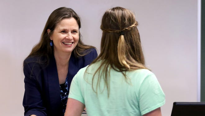"Tamara McGinnis, director of theater and assistant professor of English, speaks with Emily Abbey, a senior communications major at Corban University. Jim Hills, professor of humanities, said, ""Without fail, the kids' tone changes when they talk about Tammy McGinnis because she taps into things that they don't know are there: insights, interests and eventually some skills. Good teachers do that."""