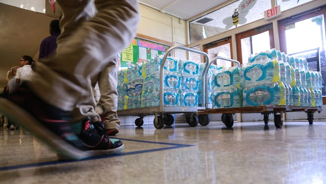 Freeman Elementary School students line up to go back to class past cases of bottle water donated to their school on Thursday, Oct. 8, 2015.