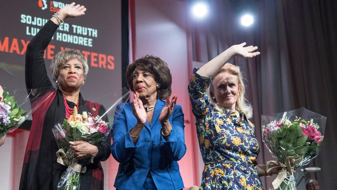 From left, Congresswomen Brenda Lawrence (D-MI), left, Maxine Waters (D-CA), and Debbie Dingell (D-MI), wave at the attendees at the Sojourner Truth Lunch at the Women's Convention at Cobo Center in downtown Detroit, Saturday, October 28, 2017.