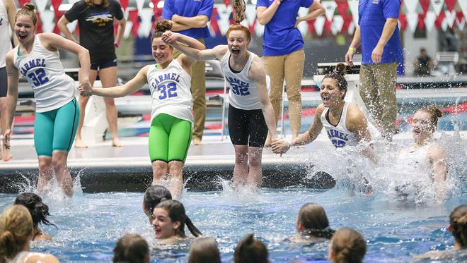 Swimmers from Carmel High School jump into the pool, a tradition after each of their 32 consecutive state titles, at IHSAA girls state swimming finals at IUPUI Natatorium in Indianapolis, Saturday, Feb. 10, 2018. The state title winning streak holds a national record.