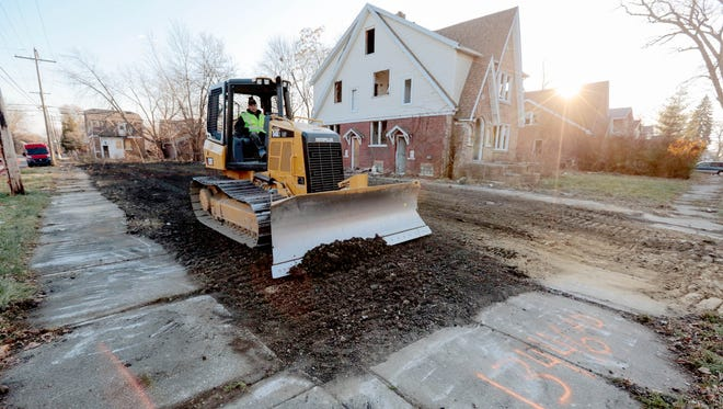 Employees of Adamo Demolition work on the final grading of a lot next to an abandoned house after another house was demolished on Elmdale Street in Detroit in December 2014.