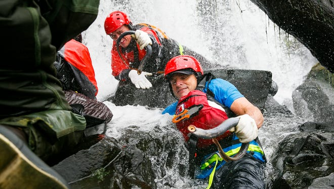 Kelly Dirksen sticks his arm deep into the water to grab lamprey as a team of four harvest the fish from Willamette Falls on Monday, July 9, 2018, in Oregon City. Dirksen is the fish and wildlife program manager for The Confederated Tribes of Grand Ronde, which operates one of the regionÕs largest lamprey restoration projects.