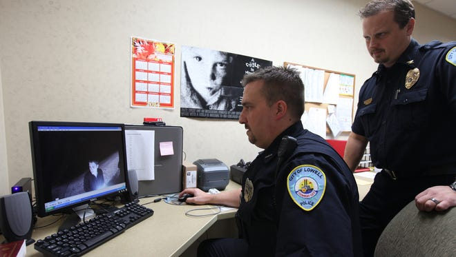 This Sept. 22, 2014 photo, In this Sept. 22, 2014 photo, detective Gordy Lauren, of the the Lowell police department, in Kent County Mich., with Chief of Police Steven Bukala, looks over his shoulder as they review the weekends camera recording. The police department in the western Michigan city of Lowell is among several around the state that are reporting positive results from the routine use of body video recorders for their officers.