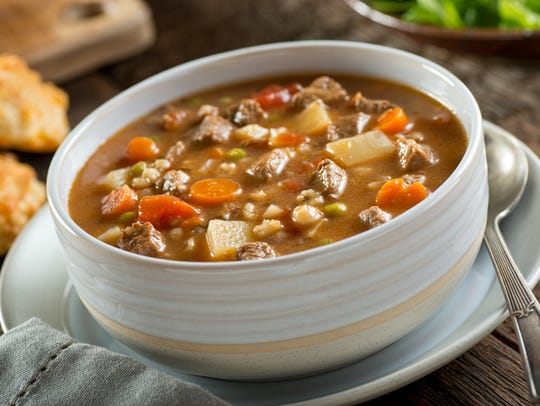 A bowl of delicious beef and barley soup with carrots,