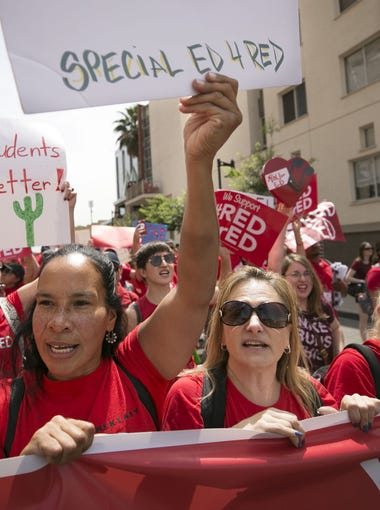 Aixa Reina (center left) and Tara Sanchez, (center right) both special education teachers at Cartwright School District #83 in Phoenix, march from Chase Field in downtown Phoenix to the Arizona capitol on the first day of the Arizona teacher walkout on Thursday, April 26, 2018.