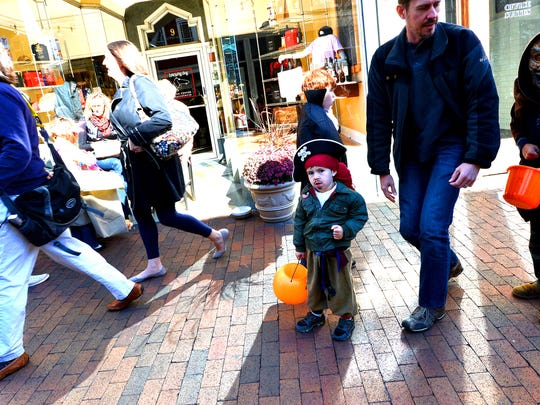 """A young """"pirate"""" looks around while walking through downtown Staunton trick-or-treating with others on Saturday, Oct. 26, 2013."""