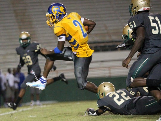 Rickards' Kelvin Dean leaps away from a Lincoln tackler during Friday's spring jamboree between Godby, Lincoln and Rickards at Florida A&M's Bragg Memorial Stadium.