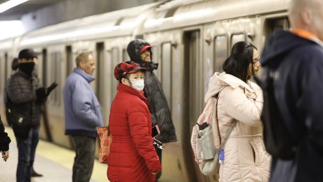 People wait to board at Quincy Center Red Line station amid the coronavirus pandemic.