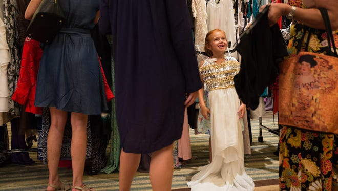 Giada Disarro, 6, hangs a dress from her shoulders during the Love That Dress! Collier event at the Naples Grande Beach Resort on Thursday Sept. 1, 2016. Attendees enjoyed music, cocktails, a silent auction and the opportunity to shop over 3,000 dresses, shoes, handbags and accessories. The proceeds from the event benefited PACE Center for Girls, Collier County.