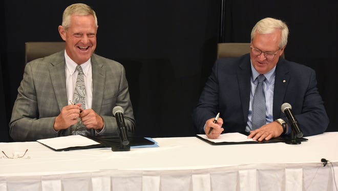 Kelby Krabbenhoft, president and CEO of Sanford Health (left) and David J. Horazdovsky, president and CEO of the Evangelical Lutheran Good Samaritan Society,  react after signing an agreement during a press conference at the Sheraton Sioux Falls & Convention Center in Sioux Falls, S.D. Tuesday, June 26, 2018.