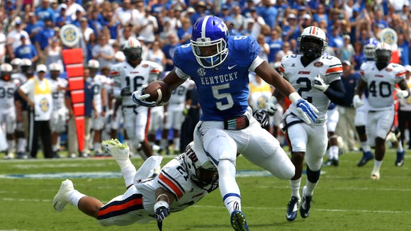Kentucky's Braylon Heard leaps out of the reach of UTM's Jordan Landry to score his second touchdown of the game.  Aug. 30, 2014