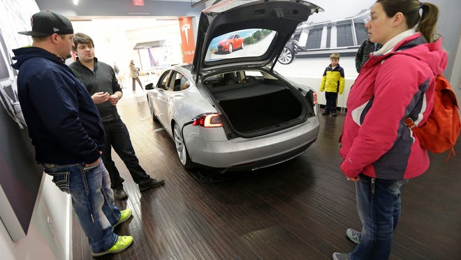 Robert Reynolds, left, and his wife, Sarah,  check out a new Tesla all-electric car with Tesla rep John Van Cleave at a Tesla showroom inside the Kenwood Towne Centre in Cincinnati.