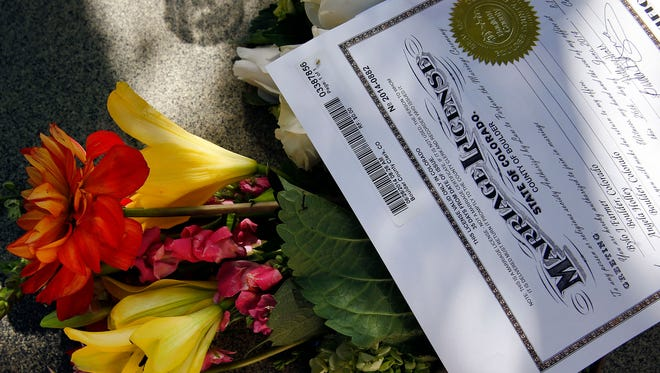 FILE - In this June 26, 2014 file photo, a bouquet of flowers sits next to the new marriage license of longtime same-sex couple Angie Holley and Bylo Farmer on a table outside the offices of the Boulder County Clerk and Recorder, in Boulder, Colo. The Supreme Court cleared the way Monday, Oct. 6, 2014, for an immediate expansion of same-sex marriage by unexpectedly and tersely turning away appeals from five states seeking to prohibit gay and lesbian unions. The court's order effectively makes gay marriage legal now in 30 states.  (AP Photo/Brennan Linsley, file)