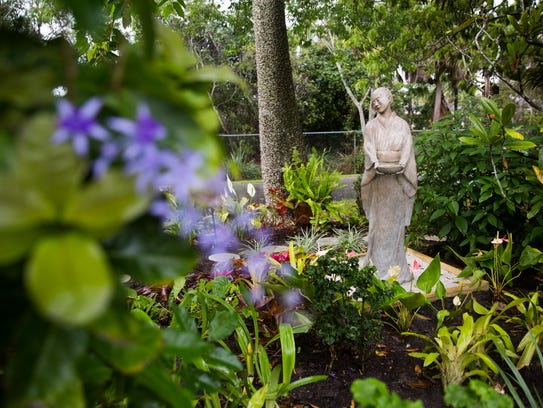 A statue sits in the rain at the community garden on