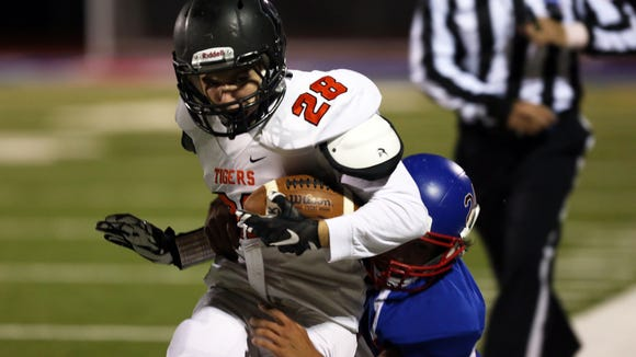 Mamaroneck's Emerson Genovese (28) gets tackled by