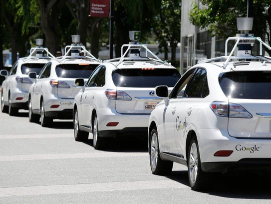 A row of Google self-driving cars is seen outside the