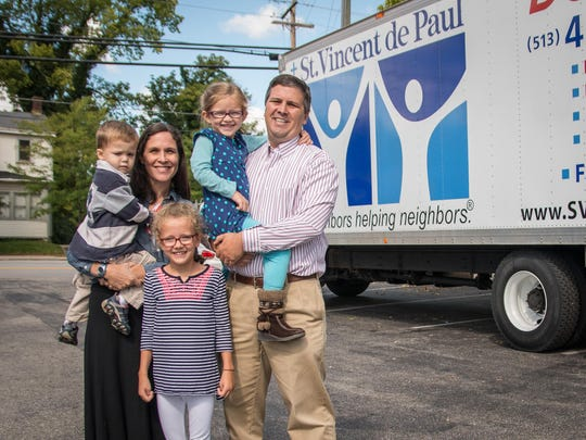 Andrew Curran, right, president of the board for St. Vincent De Paul, stands outside the Beechmont Avenue store location with his wife Liz and three children. As a way to represent his job and faith, Curran will take his family to Philadelphia later this month to see Pope Francis during his visit to the U.S. this month.