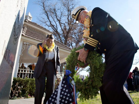 Pearl Harbor Survivors Association member and United States Air Force veteran Harris Hammersmith, left, salutes as U.S. Navy veteran Ronald D. Lewis lays a wreath at the base of the Pearl Harbor monument during a memorial service marking the 70th anniversary of the Japanese attack on Pearl Harbor at Vernon Worthen Park in St. George, Dec. 7, 2011.