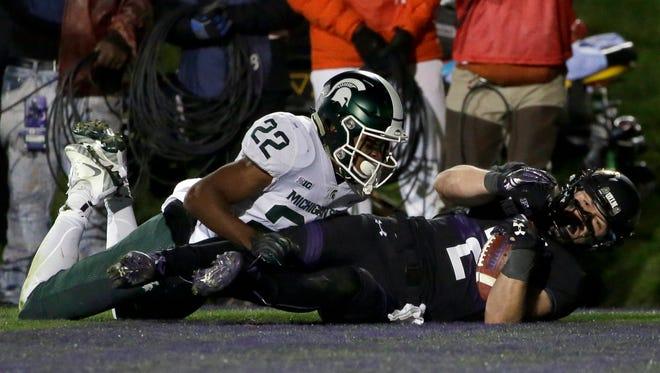 Northwestern wide receiver Flynn Nagel, right, scores a touchdown against Michigan State cornerback Josiah Scott during triple overtime.