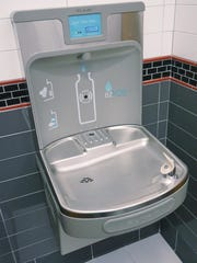The water fountain has a place to fill water bottles.