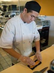 Hang Lin prepares spicy salmon roll.