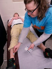 Nick Freda, a varsity boys soccer player at Plymouth High School, is prepped for an electrocardiogram by exercise physiologist Michele Bandoo.