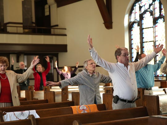 The congregation at Immanuel Baptist Church raises its hands in praise while singing hymnals together on Nov. 13, 2016. Many prayer requests concerned the state of the nation and praying for peace among all.