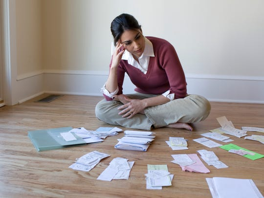 woman-looking-at-bills-receipts-paying-taxes-organizing-documents.jpg