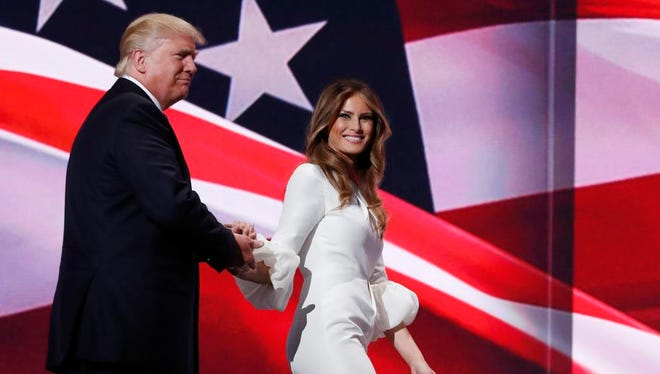 Republican presidential candidate Donald Trump, right, walks off stage with his wife Melania during the Republican National Convention, Monday.
