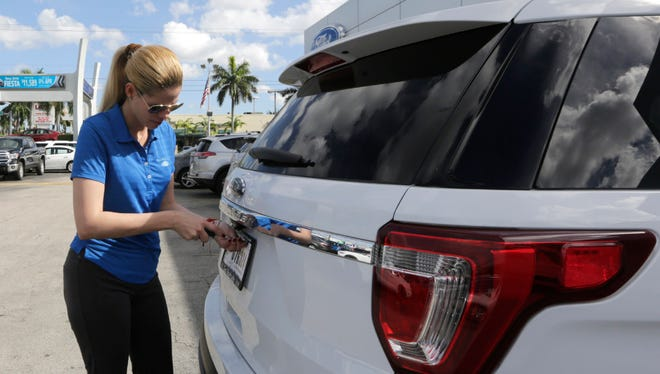 Ford sales consultant Yanaisis Milian removes the dealer tag on a sold 2017 Ford Explorer at an auto dealership in Hialeah, Fla., on Monday. Truck and SUV sales remain strong in the U.S. while car sales are weakening.