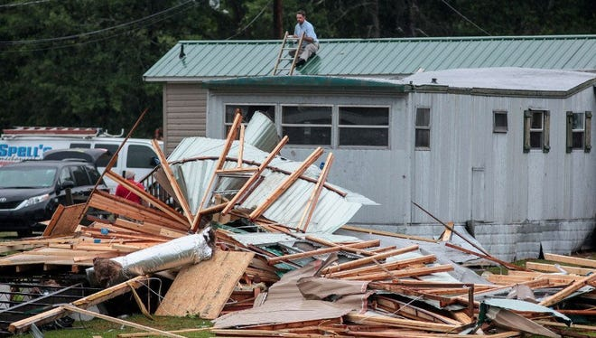 A man patches holes in his roof after a possible tornado destroyed parts of a mobile home neighborhood and a volunteer fire station in Autryville, N.C., a week ago. A spokesman for Sampson County said multiple structures have been damaged after what's believed to be a tornado touched down.