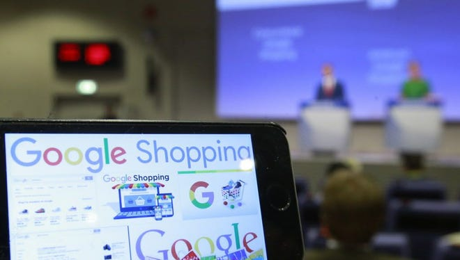 Google Shopping logos on a phone as European Commissioner for Competition Margrethe Vestager (R) speaks during a press conference on an antitrust case against Google Shopping.
